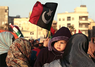 A protester holds her baby during an anti-Gaddafi demonstration in Benghazi