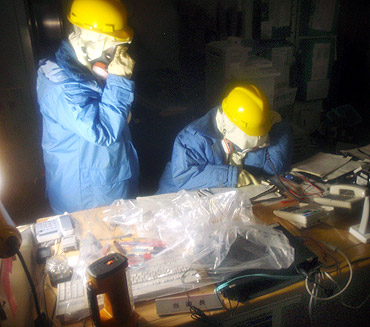 Tokyo Electric Power Co. workers record the status of instruments in a control room at the Fukushima Daiichi Nuclear Power Plant