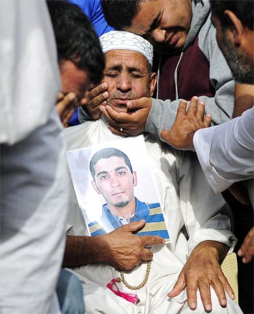 The father of activist Ahmed Farhan is comforted in Sitra. Ahmed was killed during clashes with cops