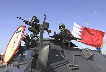 A soldier from the GCC forces flashes the victory sign as he guards the entrance to Pearl Square