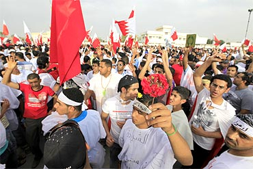 Anti-government protesters shout slogans at the gate of Bahrain King's al-Safriya Palace in Zallaq