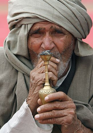 A member of the Jat community smokes hookah during a rally in New Delhi