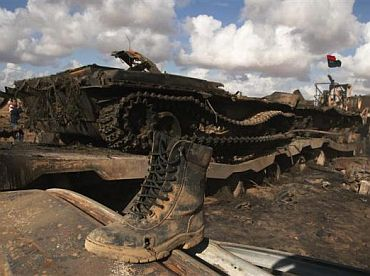 A boot belonging to a soldier loyal to Libyan leader Muammar Gaddafi is seen on a destroyed tank after an air strike by coalition forces, along a road between Benghazi and Ajdabiya