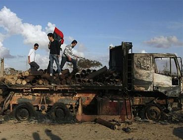 People stand atop a destroyed truck loaded with weapons belonging to forces loyal to Libyan leader Muammar Gaddafi