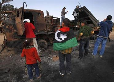 People look at weapons belonging to forces loyal to Libyan leader Muammar Gaddafi, destroyed by a coalition air strike, along a road between Benghazi and Ajdabiyah