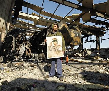 A Libyan holds a poster of Libya's leader Muammar Gaddafi at a naval military facility damaged by coalition air strikes last night in eastern Tripoli