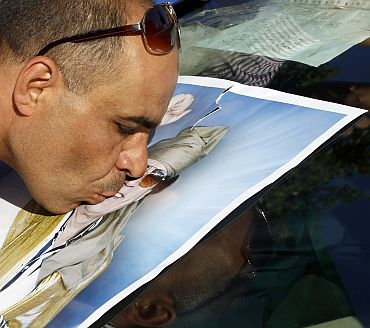 A supporter of Libya's leader Muammar Gaddafi kisses a picture of Gaddafi during a protest in front of the United Nations office in Tripoli