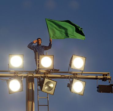 A supporter of Libya's leader Muammar Gaddafi holds a Libyan flag atop floodlights at Green Square in Tripoli