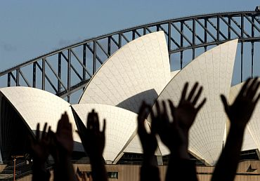 Yoga enthusiasts perform sun salutations in front of Sydney's Opera House and Harbour Bridge in Australia