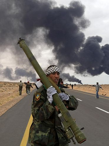 A rebel holds a rocket propelled grenade launcher during clashes with pro-Gaddafi forces between Ras Lanuf and Bin Jawad