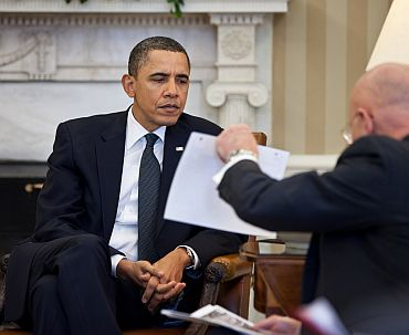 President Barack Obama studies a document held by Director of National Intelligence James Clapper during the Presidential daily briefing