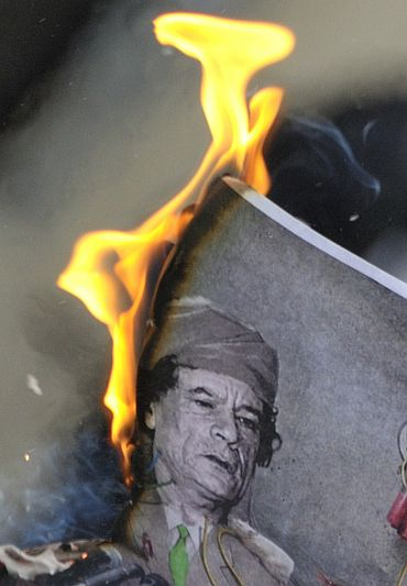 A man burns a picture of Libyan leader Muammar Gaddafi during a demonstration