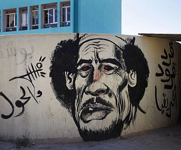 Revolutionary graffiti caricaturing Muammar Gaddafi adorns a wall in Benghazi