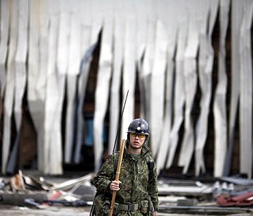 A member of Japan Self Defense Force walks in front of a destroyed building at the port of Kesennuma
