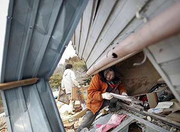 A woman retrieves belongings from her home destroyed in a tsunami at the port of the island of Oshima