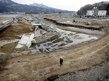 A man stands next to the damaged seawall of Miyako town, Iwate Prefecture