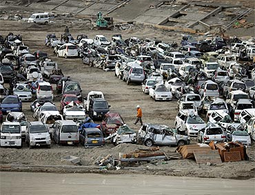 Vehicles destroyed by the earthquake and tsunami are seen at a car dump in Miyako town, Iwate prefecture