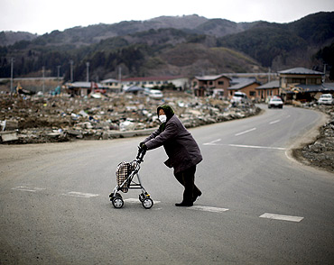 A woman crosses a street at an area destroyed by the earthquake and tsunami in Yamada town, Iwate Prefecture