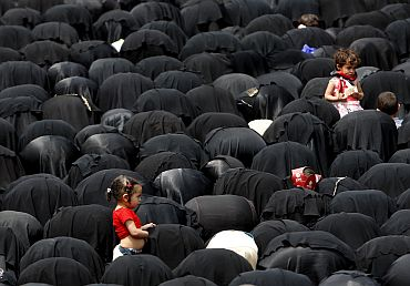 A girl stands beside women who are praying during an anti-government rally to demand for the ouster of Yemen's President Ali Abdullah Saleh in Sanaa University