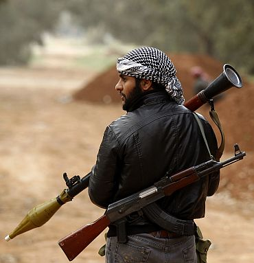 A rebel fighter holds a RPG launcher in Benghazi