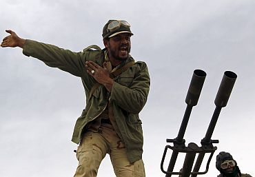 A rebel fighter reacts upon incoming shells fired by soldiers loyal to Libyan leader Muammar Gaddafi during a battle in Ajdabiya
