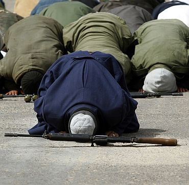 Rebel fighters pray before a battle on the road between Ras Lanuf and Bin Jawad
