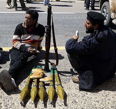 Rebel fighters take a break along the Benghazi-Ajdabiyah road, near Ajdabiya