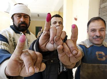 Egyptian men display their ink stained fingertips after casting their votes for a referendum on constitutional amendments at a polling station in Cairo