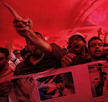 Protesters shout slogans while standing underneath Bahrain's national flag during a protest against Bahrain's King Hamad bin Isa Al-Khalifa