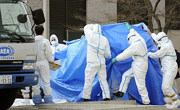 Japan Self Defense Force members in protective clothing prepare to transfer to another hospital workers who were exposed to radiation