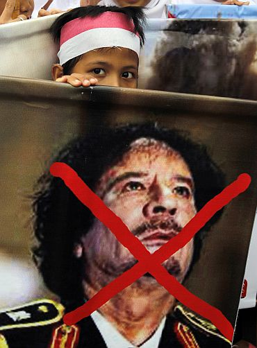A child carries an poster denouncing Libyan leader Muammar Gaddafi
