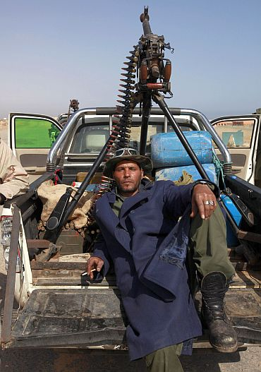 A rebel fighter rests on the road between Ras Lanuf and Bin Jawad in Libya