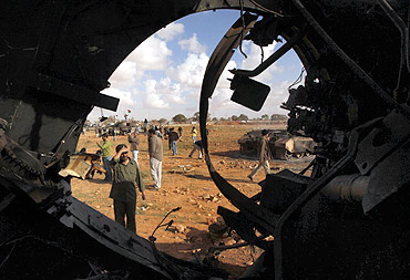 A man looks at a destroyed tank belonging to Gaddafi's forces after an air strike by coalition forces