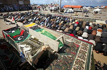 Mourners pray next to coffins containing bodies of Libyans killed by Gaddafi's forces during a funeral in Benghazi