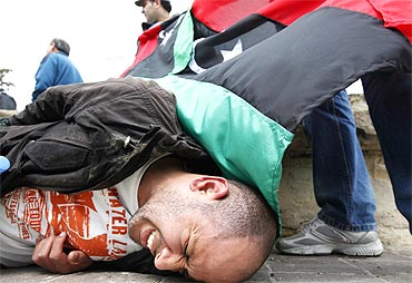 An injured anti-Gaddafi protester lies on the ground after clashes with the police