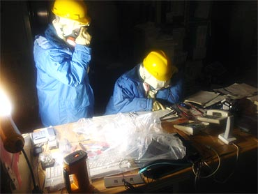 Handout photo from the Japan's Nuclear and Industrial Safety Agency shows Tokyo Electric Power Co. workers recording the status of instruments in a control room at the Fukushima Daiichi Nuclear Power Plant