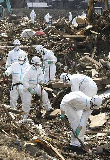 Police officers wearing protective suits search for victims of the earthquake and a tsunami in Fukushima prefecture in Minamisoma City, about 30km north of the crippled Fukushima Daiichi Nuclear Power Station