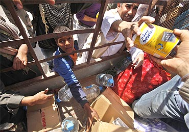 Libyans gather to receive food bring distributed by a local resident in Ajdabiyah on Sunday