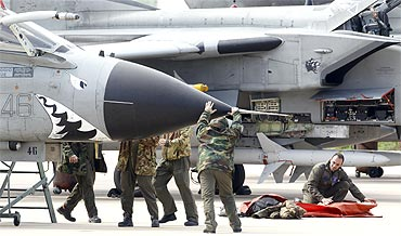 Italian ground crew work on a Tornado jet fighter plane. NATO ambassadors approved an operations plan for the alliance to help enforce a UN arms embargo on Libya on Sunday, a NATO statement said