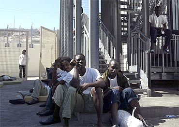 Migrants sit inside the main gate of a holding centre in Italy