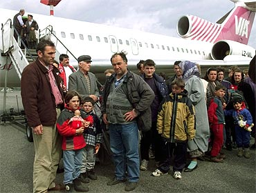 Albanian refugees waits in a queue after they disembark from a plane at Berlin's Schoenefeld airport