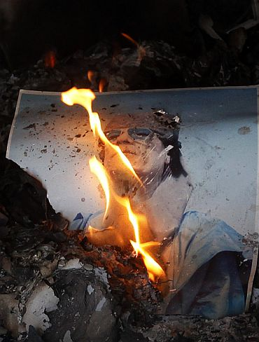 A burning picture of Libyan leader Muammar Gaddafi