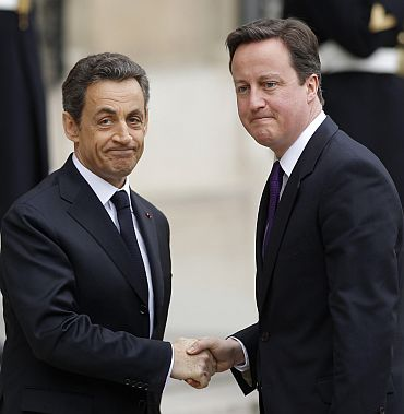 France's President Nicolas Sarkozy greets Britain's Prime Minister David Cameron at the Elysee Palace ahead of wider international talks on Libya in Paris