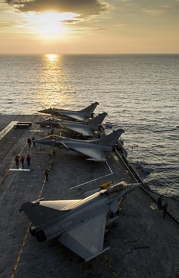 A French naval crew prepares Rafale fighter jets aboard the Charles de Gaulle aircraft carrier