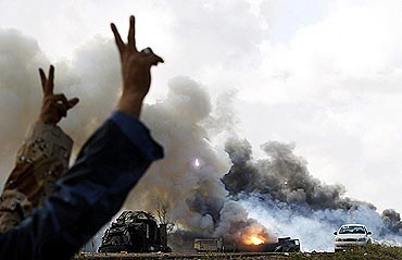 Rebel fighters gesture in front of burning vehicles belonging to Gaddafi's forces after an air strike by coalition forces along a road between Benghazi and Ajdabiyah in Libya