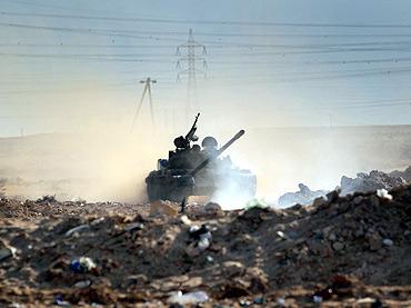 A  Libyan rebel tank advances  advances across the battlefield towards government troops