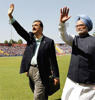 Gilani and PM Manmohan Singh wave to spectators prior to the start of the 2011 ICC World Cup second Semi-Final between India and Pakistan at Mohali