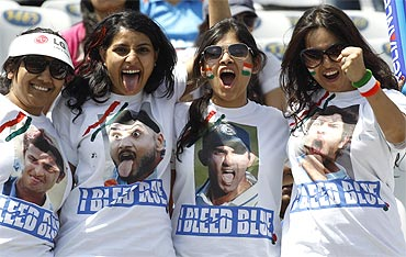 Fans of India pose wearing T-shirts with the faces of Indian players before the start of the match at Mohali