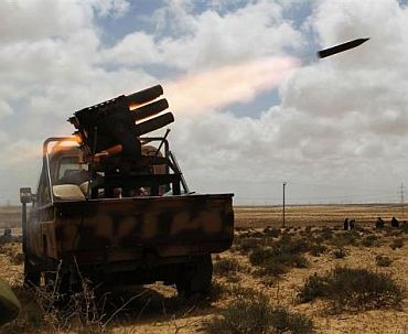 Rebels fire rockets as they return fire towards forces loyal to Muammar Gaddafi near Brega in eastern Libya