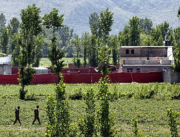 Pakistani soldiers walk past a compound, surrounded in red fabric, where locals reported a firefight took place overnight in Abbotabad